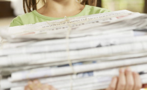 girl recycling newspapers